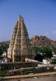 The Virupaksha Temple (also known as the Pampapathi Temple) is Hampi's main centre of pilgrimage. It is fully intact among the surrounding ruins and is still used in worship. The temple is dedicated to Lord Shiva, known here as Virupaksha, as the consort of the local goddess Pampa who is associated with the Tungabhadra River.<br/><br/>  Hampi is a village in northern Karnataka state. It is located within the ruins of Vijayanagara, the former capital of the Vijayanagara Empire. Predating the city of Vijayanagara, it continues to be an important religious centre, housing the Virupaksha Temple, as well as several other monuments belonging to the old city.
